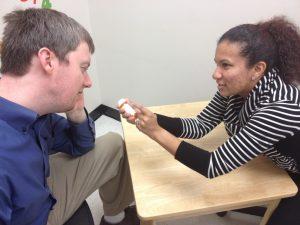 woman shows a medical prescription bottle to a man