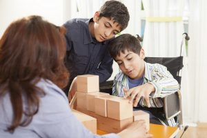 Photo of a boy helping his brother stack wooden blocks