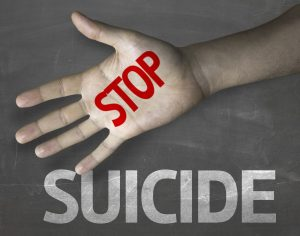 """Photo of hand with """"stop suicide"""" written on it."""