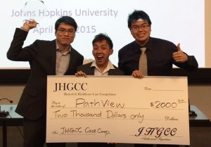 Byung-Hak Kang, Weijie Poh, and Joshua Wang pose with their first prize check for $2,000 from the JHGCC Biotech and Healthcare Case Competition