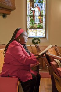 A photo of a woman reading the Bible inside of a church.