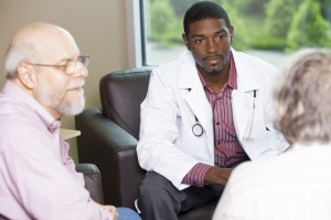 A doctor talks to an elderly couple.