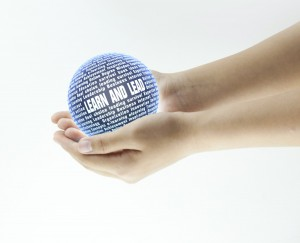 Photo of a  person holding a ball made up of leadership words and phrases.