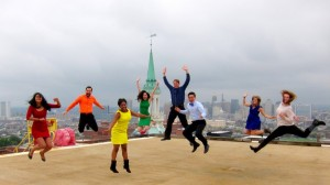 A group of students jumping up on a rooftop at the same time.