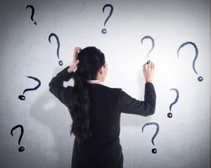 A businesswoman writes question marks on a wall