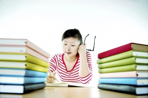 Surrounded by textbooks, a student works on a paper