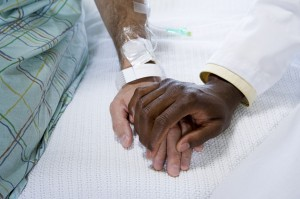 A doctor holding a patient's hand.