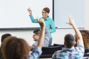 A professor asks students questions in a lecture hall