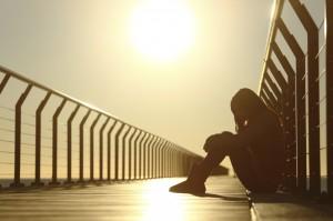 girl sitting on a bridge at sunset
