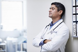 a doctor reflecting with his eyes closed