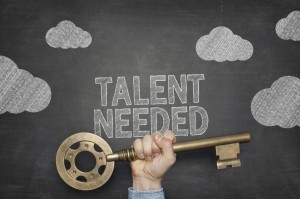 "A blackboard with the words ""Talent Needed"" written in chalk"