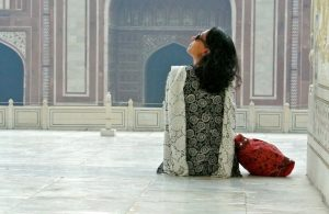 Aparna Krishnan sits in front of an indian temple