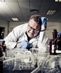 scientist in the lab is distressed while looking at overturned beakers
