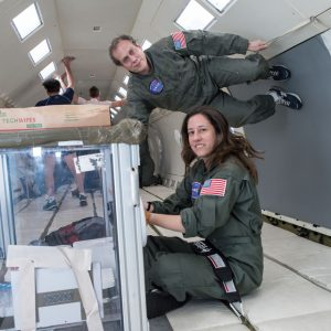 "Lindsay Rizzardi and Andy Feinberg practice pipetting at zero gravity on the ""Vomit Comet."""