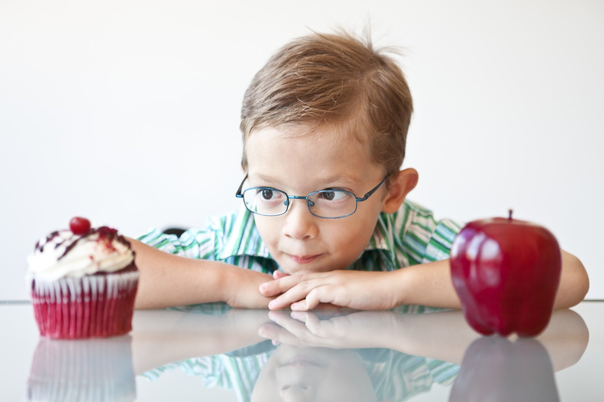 boy stares at a cupcake that's placed next to an apple