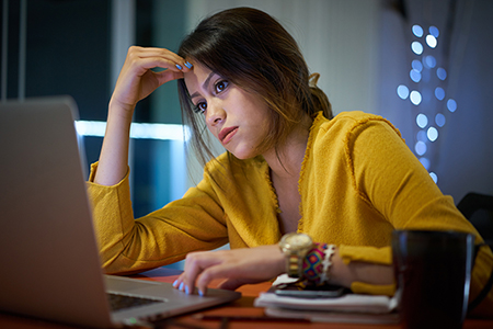 Young woman with laptop computer for homework. Tired hispanic girl and college education. Female student studying and using pc at home getting headache