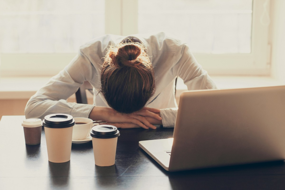 tired woman with her head on her desk
