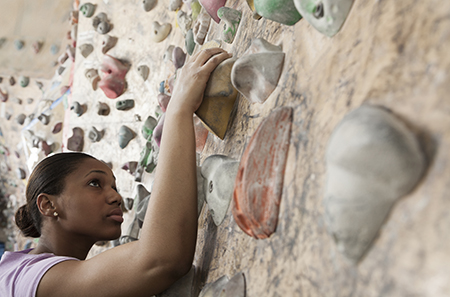Woman climbing up a wall