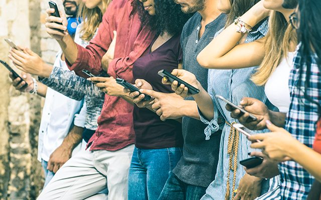 Group of multicultural friends using smartphone outdoors - People hands addicted by mobile smart phone - Technology concept with connected men and women - Shallow depth of field on vintage filter tone