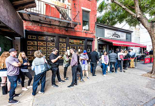 Long line of people waiting to be seated at a restaurant.