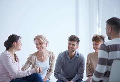 A group of young people sit and talk together.