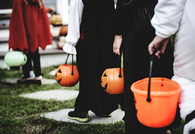 Trick-or-treaters line up at the front steps, waiting for candy.