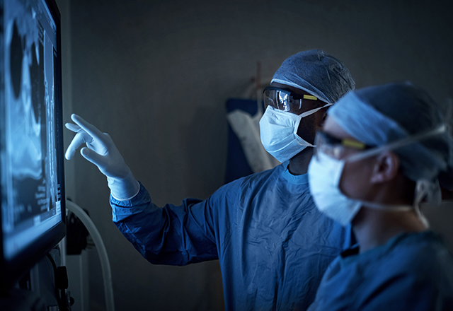 Two surgeons analyzing a patient's medical scans.