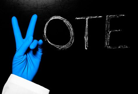 "The word ""Vote"" is written on a blackboard, with a blue latex-gloved hand making the letter V."