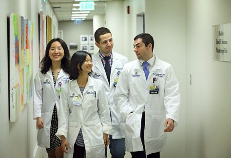 A group of Dermatology residents walk down the hall together.