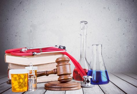 A pile of books and a wooden gavel are arranged on a table, along with medication bottles and lab beakers.