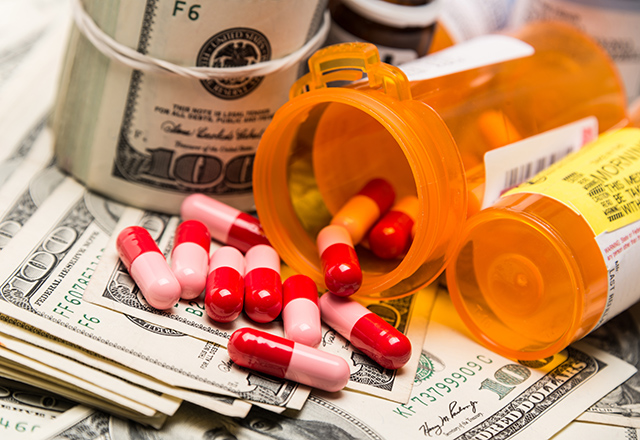 100 dollar bills, pills, and medicine containers