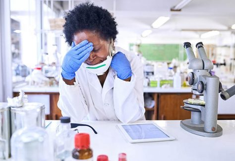 Shot of a female scientist looking stressed out while working in a lab
