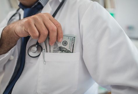 Doctor putting money in his pocket in his office, cropped photo.