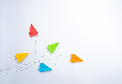 Color paper airplanes on white background.