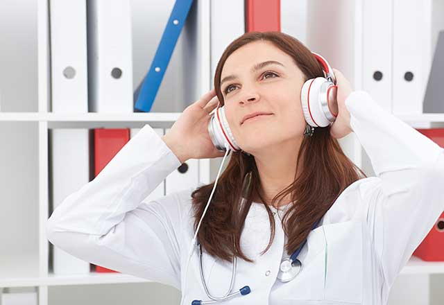 A young woman in a doctor's coat listens to music using headphones.