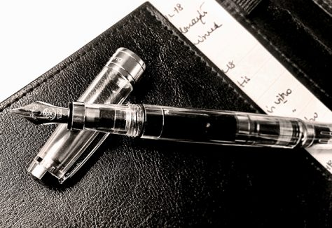 A black-and-white image of a fountain pen resting atop a notebook, taken by the author.