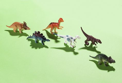 Dinosaur toys on green background