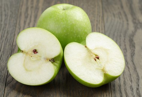Green apples on a cutting board.