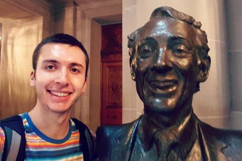David Ottenheimer poses with the statue of Harvey Milk in San Francisco City Hall.