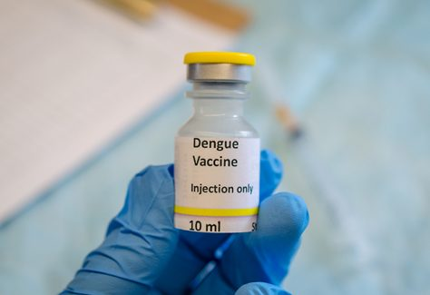A gloved hand holds a dengue vaccine vial.