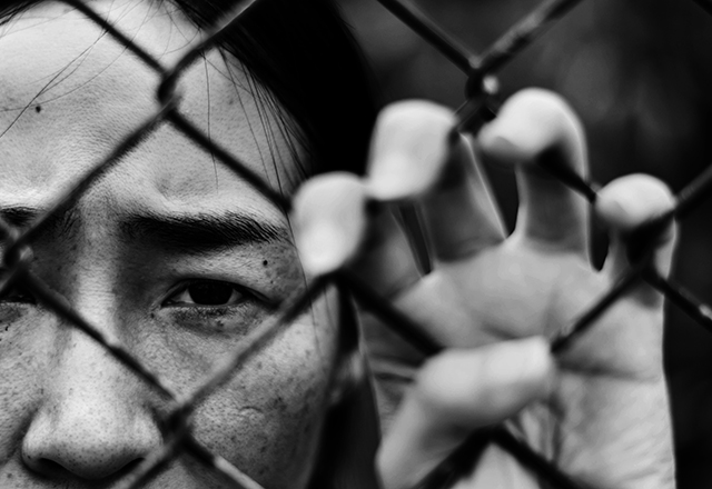 A young woman stands behind a chainlink fence.