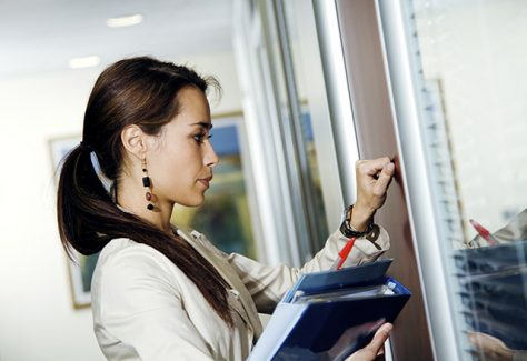 A woman steels herself as she knocks on an office door.