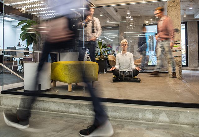 Young businesswoman meditating on the floor at her office while colleagues are walking in blurred motion. The view is through the glass.