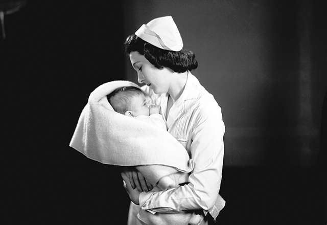 A 1950s-era nurse holds a baby, swaddled in a blanket.