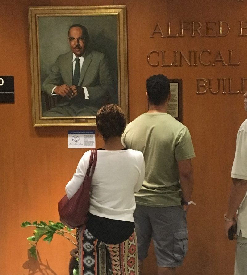 A family observes the portrait of Vivien Thomas.