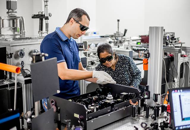 A mentor explains to a student how to use a high frequency laser for new materials research.