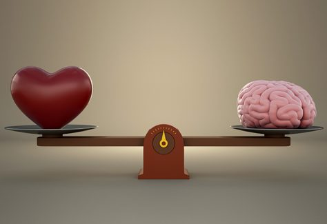 Brain and heart on a wooden balance scale.