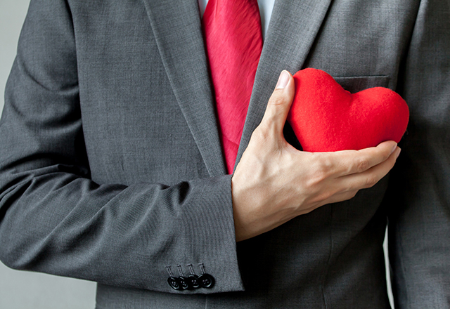 Businessman holding a red felt heart to his chest.