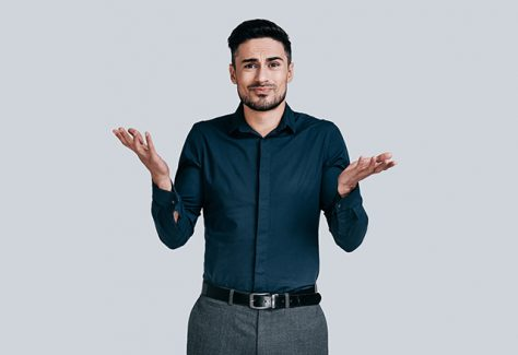 Confused young man shrugging shoulders and making face while standing against grey background