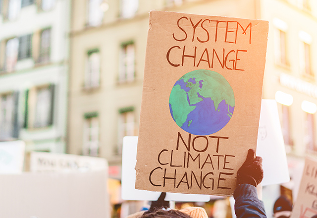 "A demonstrater holds up a sign that says, ""System change, not climate change."""